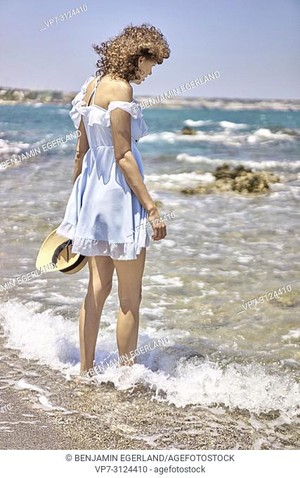 woman on beach, wearing dress, sunhat, summer, in Hersonissos, Crete, Greece