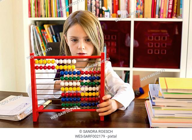Girl using abacus at home