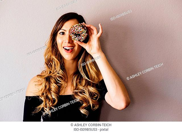 Portrait of young woman with long blond hair holding doughnut hole over eye