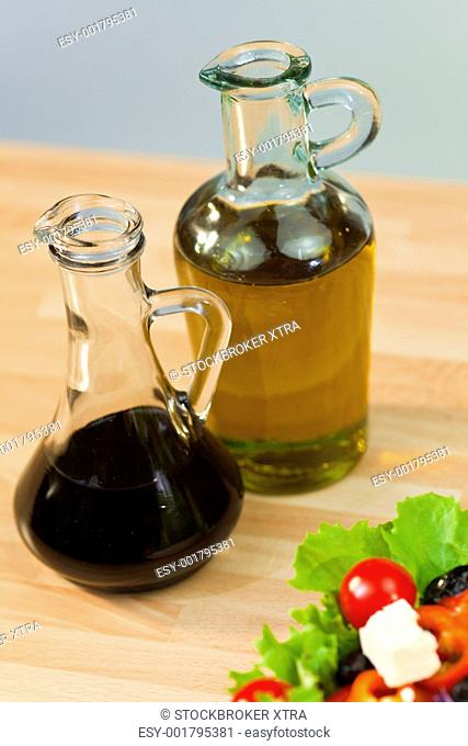 Bottles of olive oil and balsamic vinegar dressing with fresh lettuce tomato pepper olive red onion and feta cheese salad