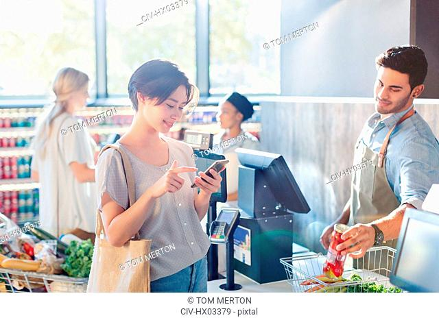 Young woman using cell phone at grocery store market checkout