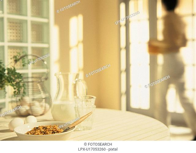 Cereal, milk and eggs on breakfast table