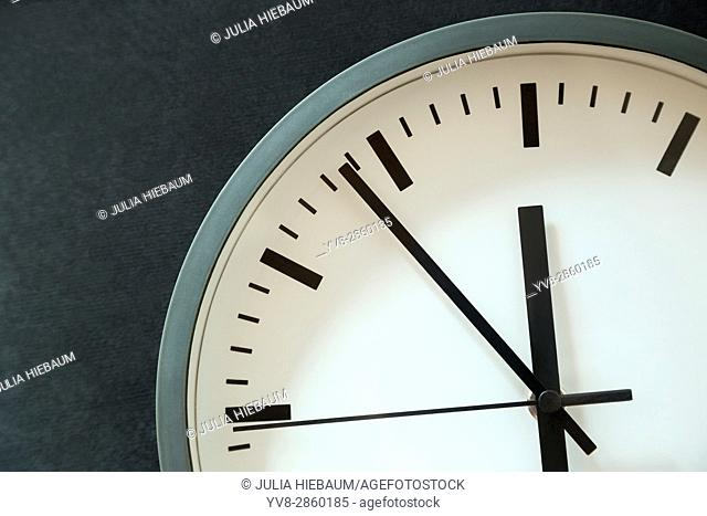 Clock showing six minutes to twelve