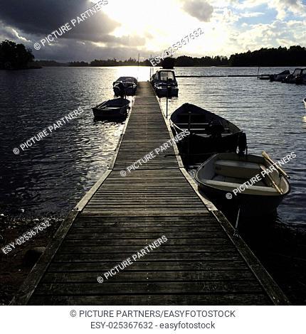 Small boats fixed on a boat dock at sundown