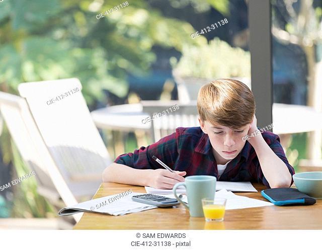 Boy doing math homework at dining table