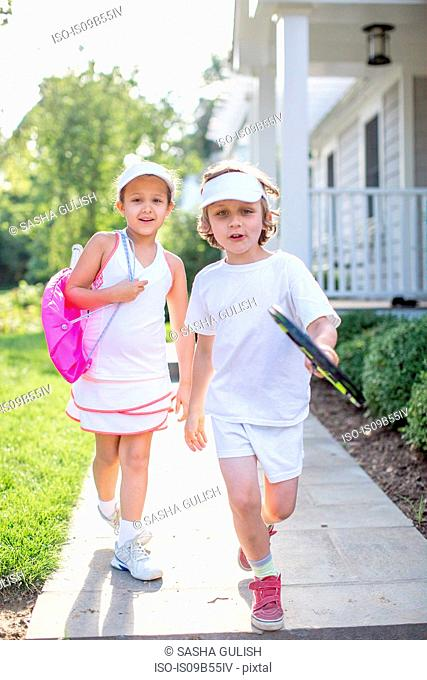 Portrait of boy and girl tennis players on garden path