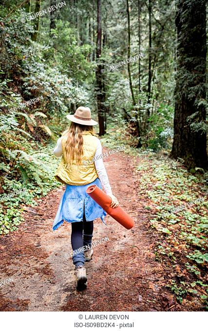 Young woman in trilby strolling in forest, rear view