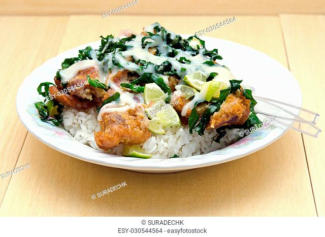 Fried chicken with lemon sauce served with herb over rice (famous thai food)