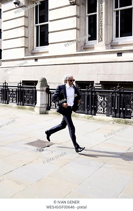 Senior businessman running on pavement in the morning