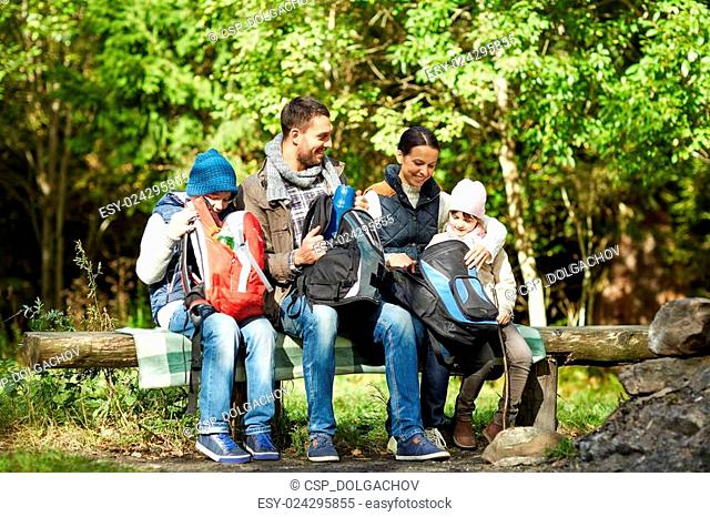 happy family with backpacks and thermos at camp