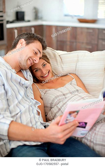 Pregnant woman reading magazine with husband