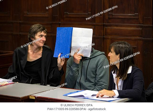 The defendant covers his face in waiting for the begin of the trial in the court room of the District Court Altona in Hamburg, Germany, 05 October 2017