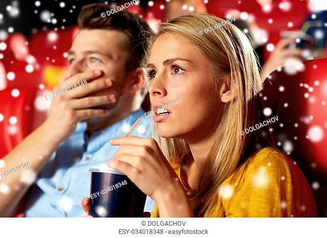 cinema, entertainment and people concept - terrified couple drinking soda and watching horror, drama or thriller movie in theater