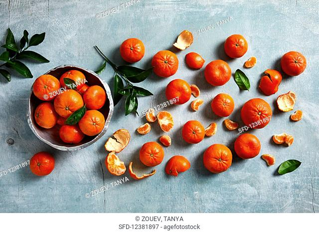 Various different sizes of mandarins, partially peeled