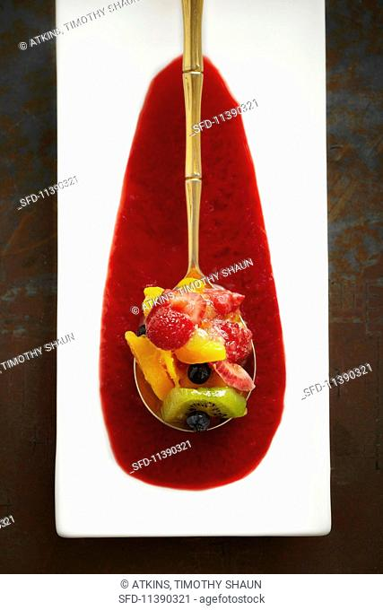 Fruit salad served on a golden spoon in a pool of sauce (seen from above)