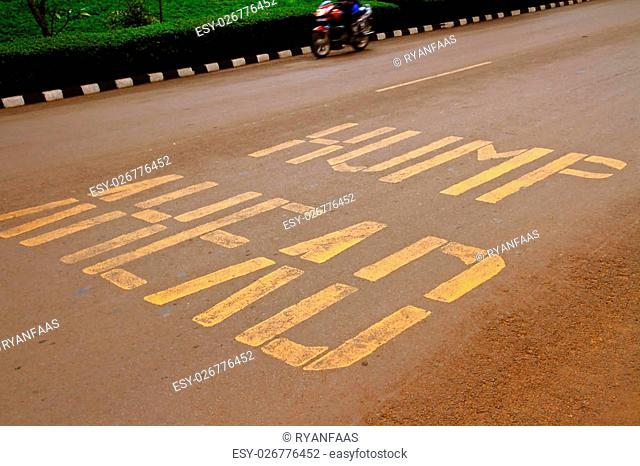 "Road warning painted on the ground warning that there is a """"hump ahead"""" in reference to a speed bump in Kigali, Rwanda, Africa"