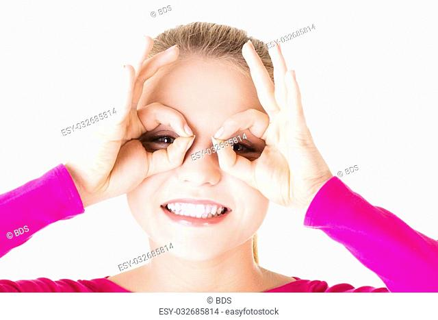 Young woman looking through imaginary binocular, isolated on white