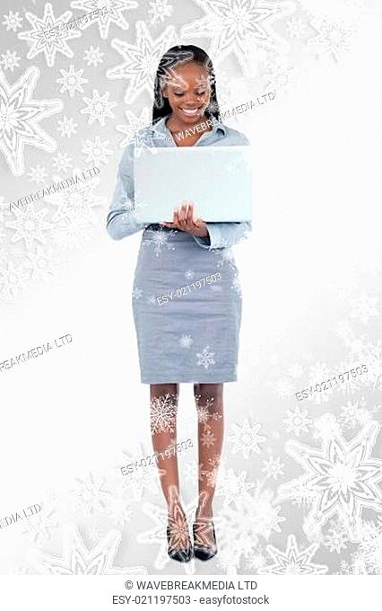 Composite image of portrait of a smiling businesswoman using a laptop while standing up