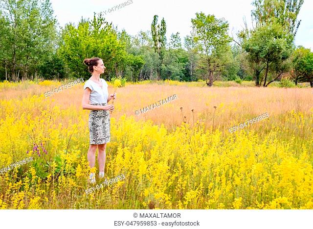 An adult woman stands up in a meadow covered with Galium verum flowers, also known as lady's bedstraw or yellow bedstraw