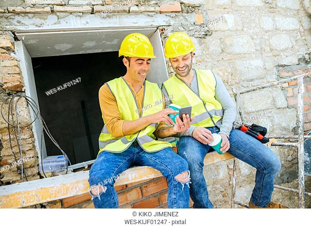 Two construction workers looking at a cell phone at break time