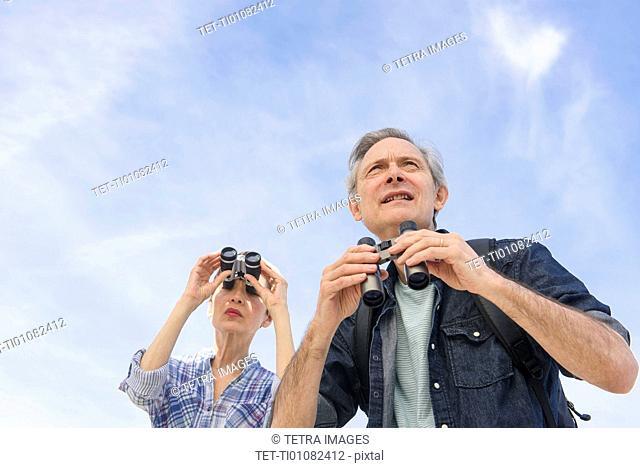 Senior couple watching birds with binoculars