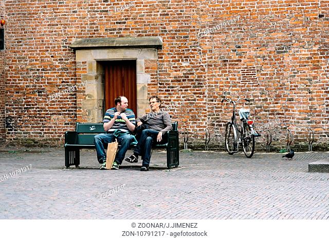 Two men sitting on a publick bench in historic centre of Utrecht, the Netherlands