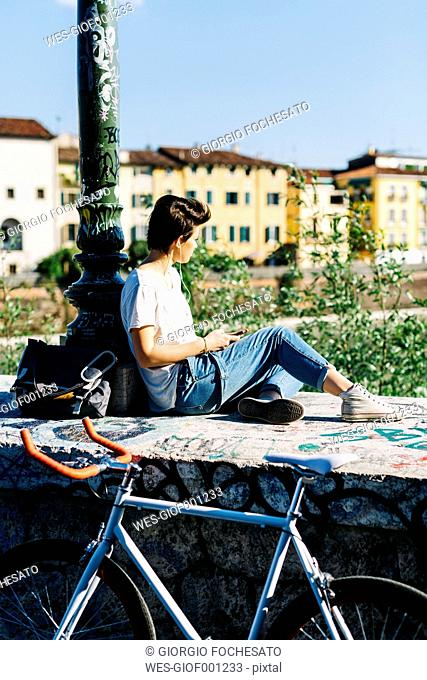 Young woman with bicycle sitting on bridge listening to music
