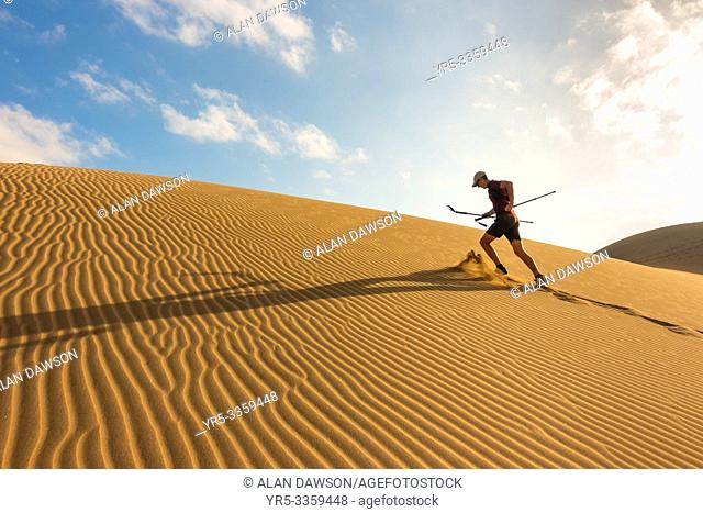 62 year old trail runner training on sand dunes at Maspalomas, Gran Canaria, Canary Islands, Spain
