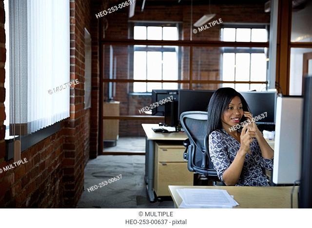 Smiling businesswoman talking on cell phone at desk