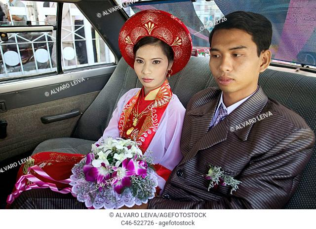 Couple going to their wedding, crossing a river by ferry. Vinh Long, Mekong Delta. Vietnam
