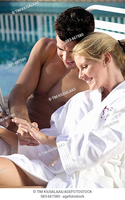 Couple sitting by pool. Woman admiring here engagement ring
