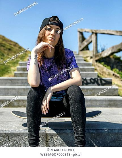 Portrait of female skate boarder with baseball cap and tattoo