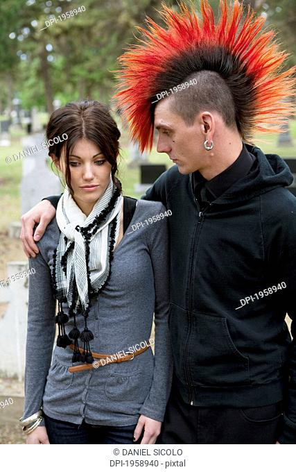 A Young Man And Young Woman Supporting Each Other In A Cemetery; Edmonton, Alberta, Canada