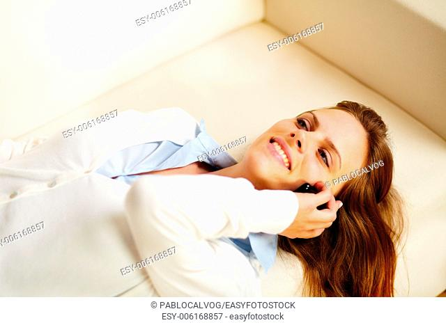 Close up portrait of a young woman lying on sofa and on the mobile phone