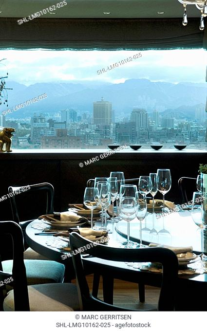 Place settings at circular dining table with view of downtown