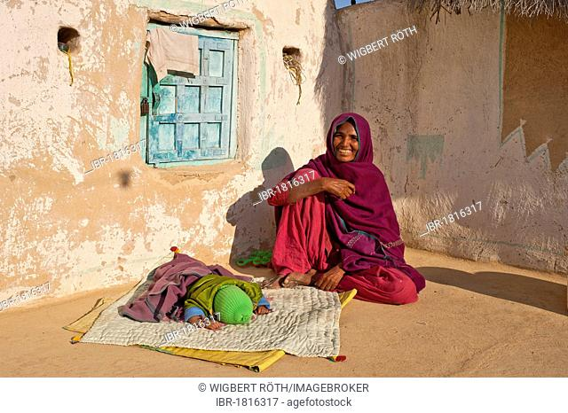 A friendly Indian woman wearing a red sari sitting on the floor in her courtyard, her sleeping child is lying in front of her on a blanket, Thar Desert
