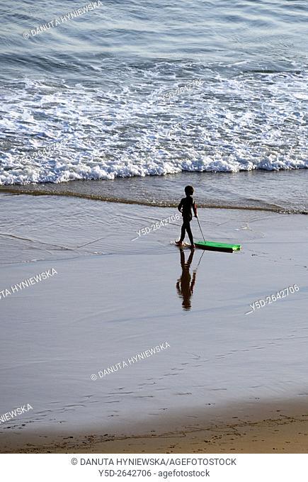 little boy in wetsuit with surfboard, Beliche Beach, Algarve, Portugal, Europe