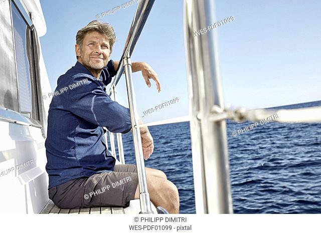 Portrait of content mature man sitting on his motor yacht