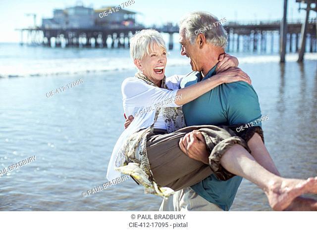 Senior man carrying wife on sunny beach