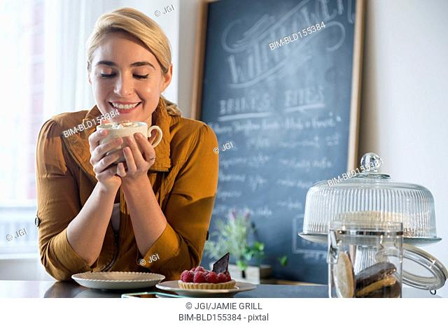 Caucasian woman smelling cup of coffee in cafe
