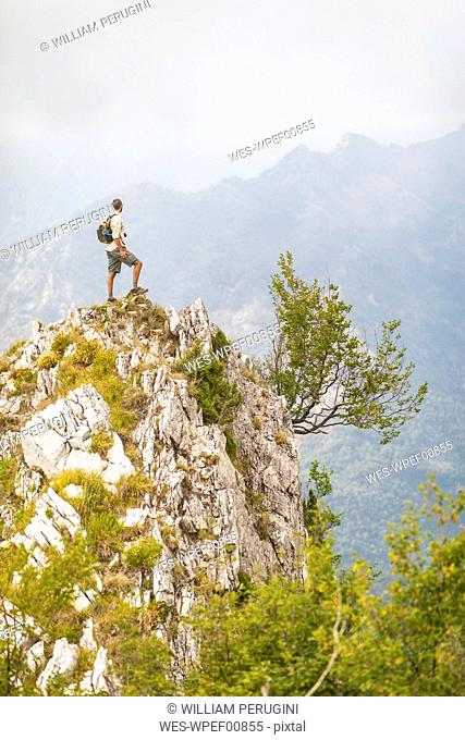 Italy, Massa, man standing on top of a peak in the Alpi Apuane mountains