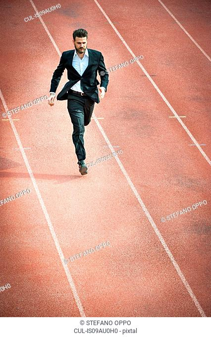 High angle view of mid adult man running on racetrack