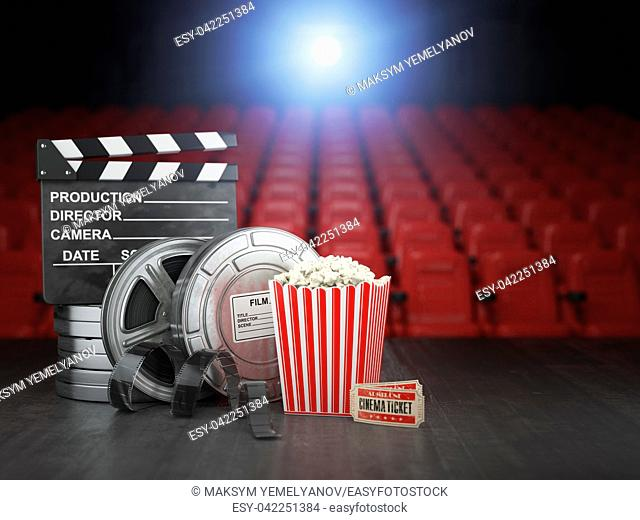 Cinema, movie or home video concept background. Film reels, clapper board and pop corn in the theater movie cinema screen with empty seats