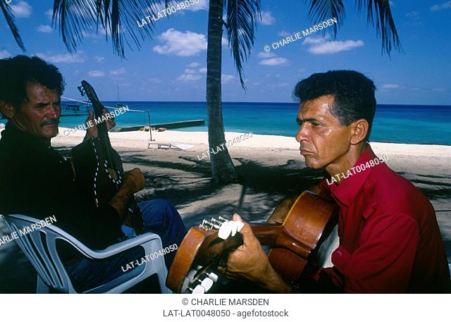 Playa Maria la Gorda. Two men playing guitar under palm tree on beach. Yacht on blue sea