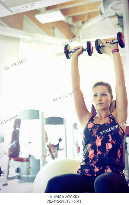 Focused woman doing dumbbell shoulder presses at gym