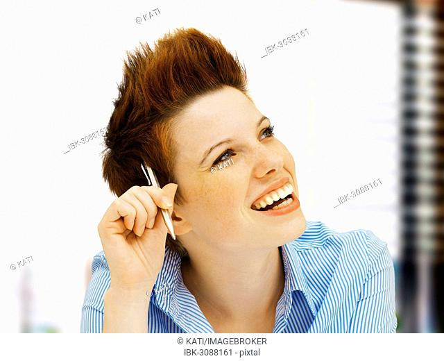 Businesswoman with a punk hairstyle in an office, smiling