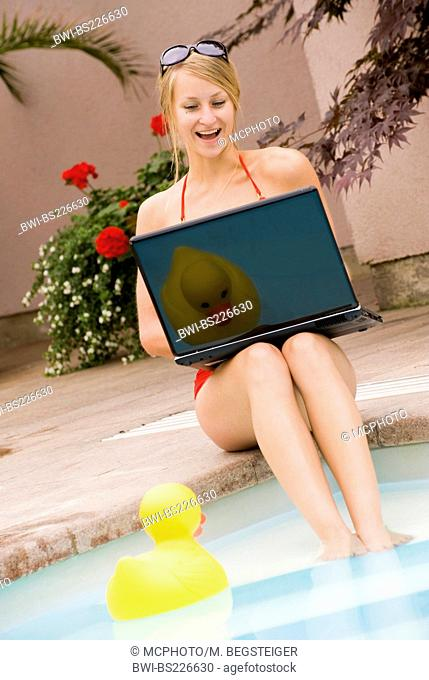 young woman using laptop at the pool