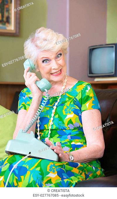 Happy senior woman in green on rotary telephone