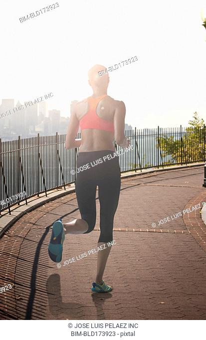 Black athlete jogging on urban waterfront
