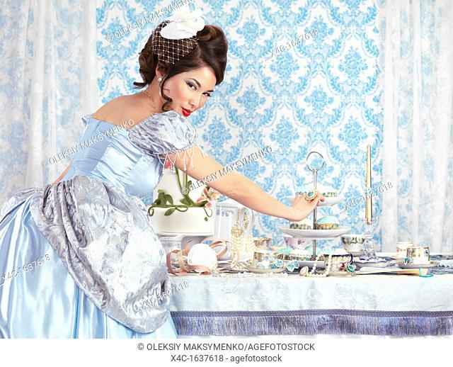 Beautiful asian lady taking a cupcake from a served tea party table